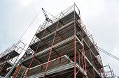 stock photo of scaffolding  - Scaffolding with a crane on a construction site, view from below