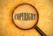 stock photo of plagiarism  - Magnifying glass focused on the word copyright - JPG