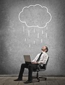 image of rain cloud  - young businessman work with laptop under a rain cloud - JPG
