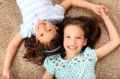 stock photo of little sister  - Cute little girls laying on the carpet - JPG