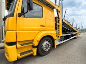 stock photo of truck-cabin  - yellow car carrier truck with raised ramp - JPG