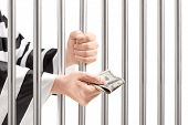 picture of prison uniform  - Man in jail holding prison bars and giving bribe isolated on white background - JPG