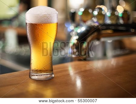 Photo of cold beer glass on a bar. Closeup.