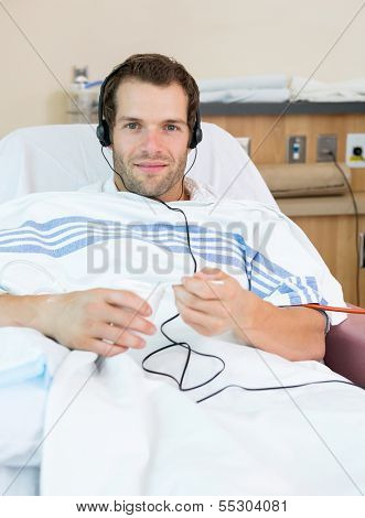 Male dialysis patient eating ice and listening to music