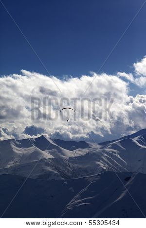 Winter Mountain In Evening And Silhouette Of Parachutist