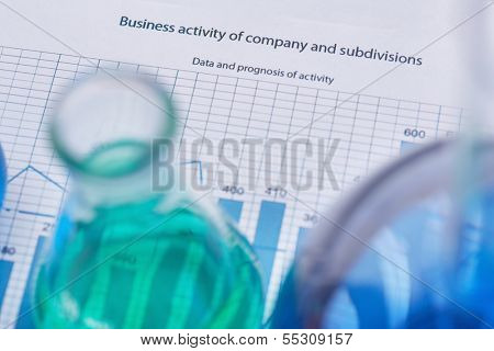Test-tubes with liquids over business document