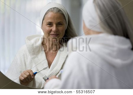 Senior woman brushing her teeths in front of the mirror