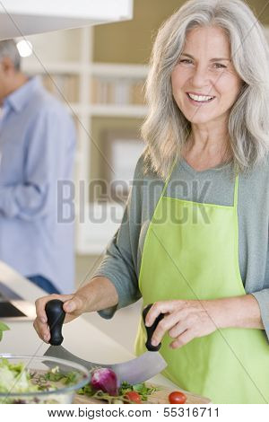 Happy senior woman cooking healthy food