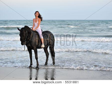 Chica de montar a caballo en la playa