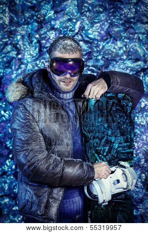 Smiling handsome man dressed in winter clothes, holding snowboard, covered with snow.