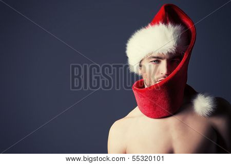 Portrait of a handsome sexual young man in Christmas hat. Copy space.