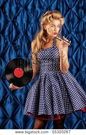Pretty pin-up woman singing with vinyl record over vintage background.