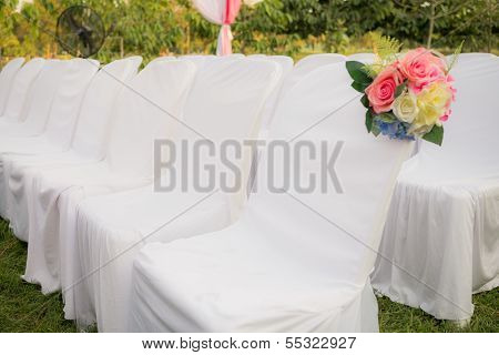 Empty White Chairs In Outdoor Wedding