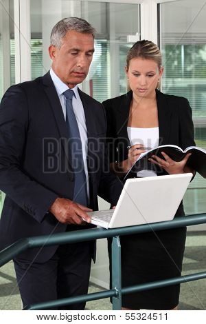 businessman and businesswoman verifying data