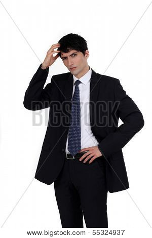 Confused businessman scratching head