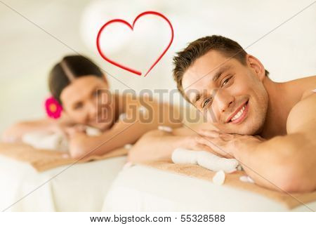 spa, beauty, love and happiness concept - smiling couple lying on massage table in spa salon