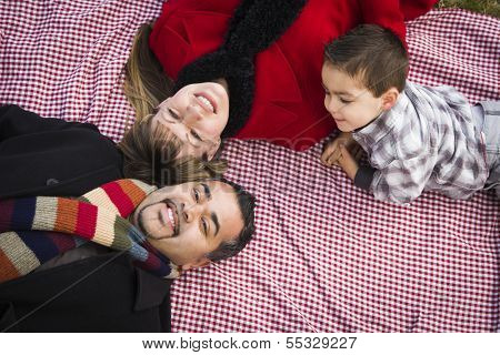 Young Mixed Race Family in Winter Clothing Laying on Their Backs on Picnic Blanket in the Park Together.