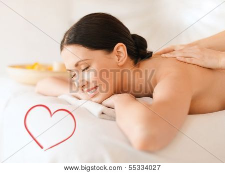 health and beauty, resort and relaxation concept - smiling woman in spa salon getting massage