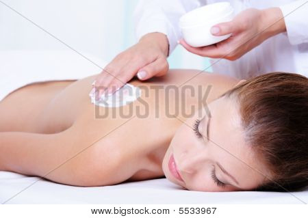 Applying  Moisturizing Cream On The Female Back