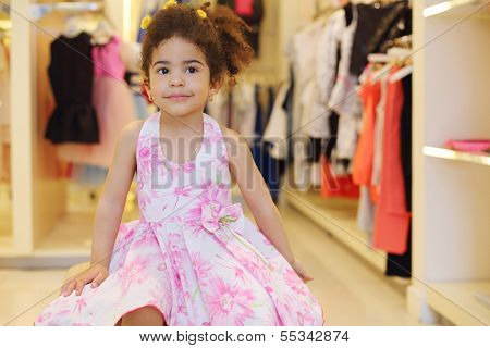 Little pretty girl in dress sits in children store with clothes for girls.