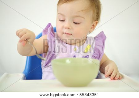 Little cute baby sits at highchair and eats porridge on plate. Shallow depth of field.