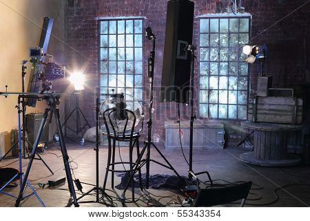 Studio with studio with brick walls and ragged windows, spotlights, camera with special devices for shooting video.