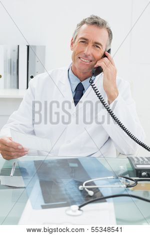 Portrait of a smiling male doctor using telephone at the medical office