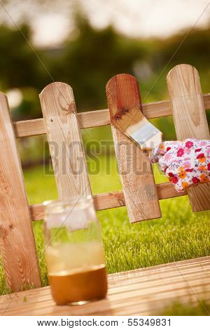 Applying protective varnish to a wooden fence