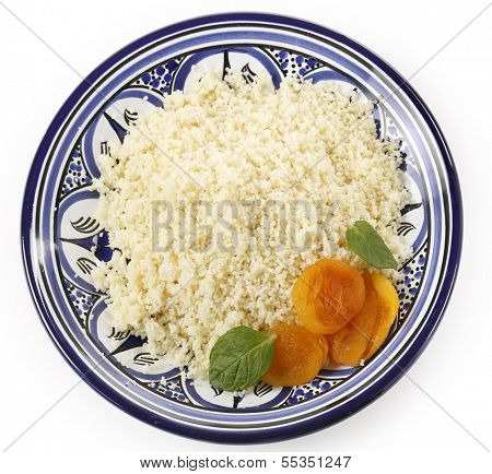 Plain couscous on a Tunisian handmade and hand-painted plate garnished with dried apricots and mint leaves, viewed from above