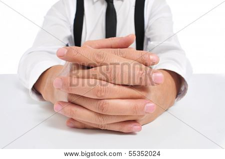 businessman sitting in a table with clasped hands
