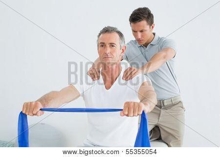 Male therapist massaging mans shoulder in the gym at hospital