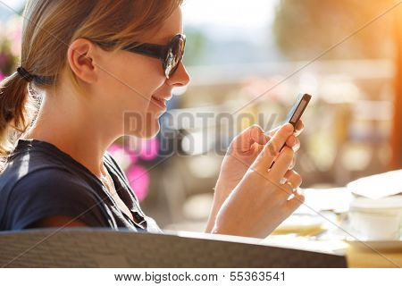 Portrait of happy woman reading off touch phone in cafe outdoors.