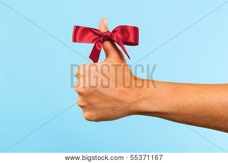 Merry Christmas like concept on blue background. Hand making like sign with a red bow