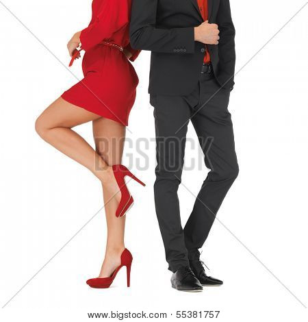 fashion, beauty and clothing concept - man in suit and woman in red dress