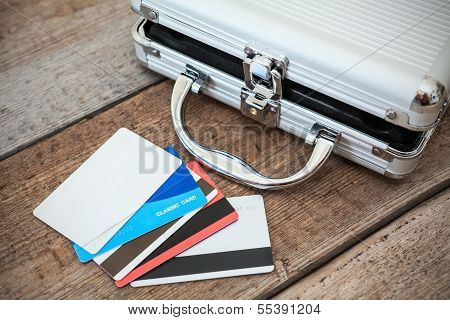 Opened Steel Case And Credit Cards On Wooden Floor