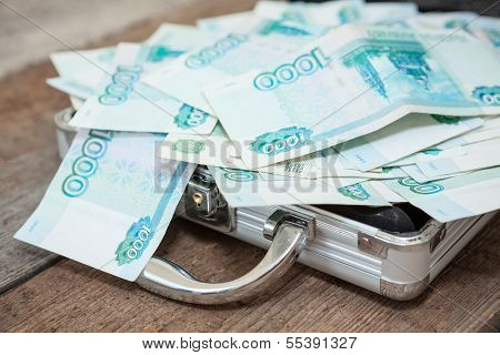 Opened Steel Case With Russian Banknotes Inside On Wooden Floor