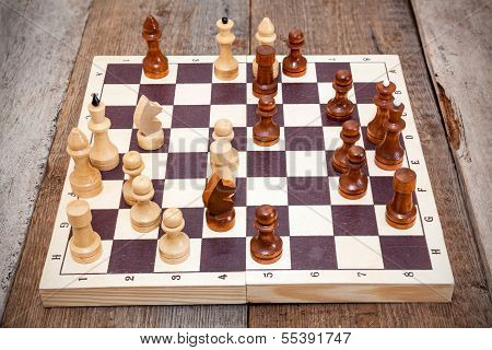 Chess Board With Wooden Figures On Floor