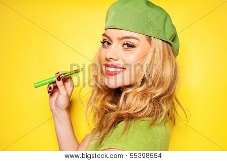 Trendy beautiful blond woman in a stylish green ensemble with an e-cigarette in her hand turning to smile at the camera, over yellow