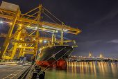 pic of shipyard  - Landscape of Container Cargo freight ship with working crane bridge in shipyard at dusk for Logistic Import Export background - JPG