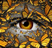 stock photo of monarch  - Communication freedom business and lifestyle concept with a close up of human eye and a group of monarch butterflies flying as a creative metaphor for the liberty of imagination expression and innovative vision - JPG