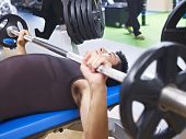 pic of work bench  - man doing bench press in fitness center - JPG