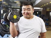 foto of obese man  - an overweight young man holding a dumbbell in fitness center - JPG