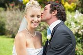 foto of full cheeks  - Husband kissing his new wife on the cheek in the countryside - JPG