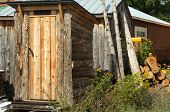 image of outhouse  - Rustic log sided outhouse sits for sale in Upper Peninsula Michigan - JPG