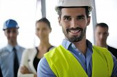 picture of blueprints  - business people group on meeting and presentation  in bright modern office with construction engineer architect and worker looking building model and blueprint  plans - JPG