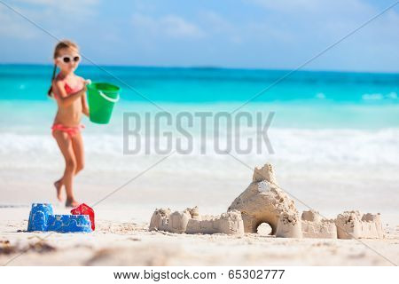 Little girl at tropical beach making sand castle, selective focus on the sandcastle
