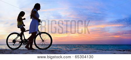 Panorama of mother and daughter with bike on a beach at sunset