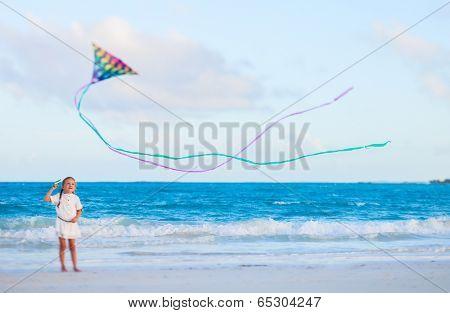 Little girl flying a kite at beach on sunset