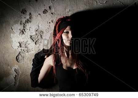 Red hair girl with dreadlocks by the wall