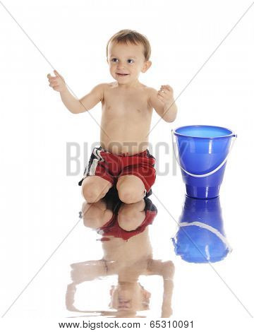 An adorable preschooler ready to catch a beach ball (not shown) as he kneels at the water's edge in his swim trunks.  On a white background.